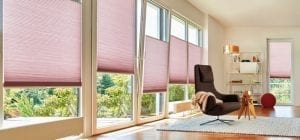 Modern living room with large tilt windows fitted with pink Duette energy saving blinds