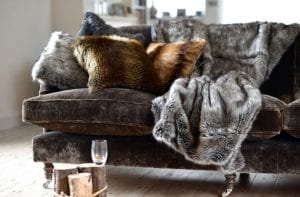 Close up of luxurious sofa with faux fur throws and cushions