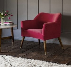 Hot pink armchair in a darkly decorated room
