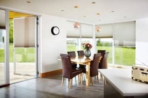 Dining area with large windows looking out to the garden fitted with Duette energy saving blinds