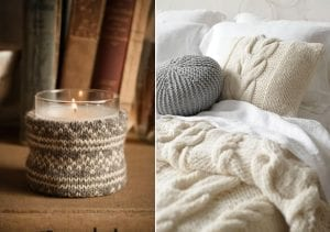 Close up of a candle and cosy bed with knitted throws and blankets