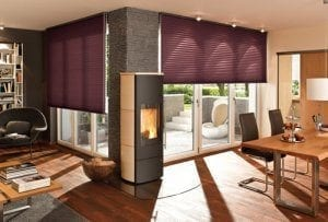 Cosy open plan kitchen and living area with windows fitted with warm berry coloured Duette blinds