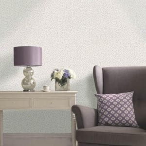 Simple living area in pastel mauve decor with armchair next to chest of drawers